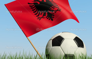 Soccer ball in the grass and the flag of Albania against the blue sky. 3d